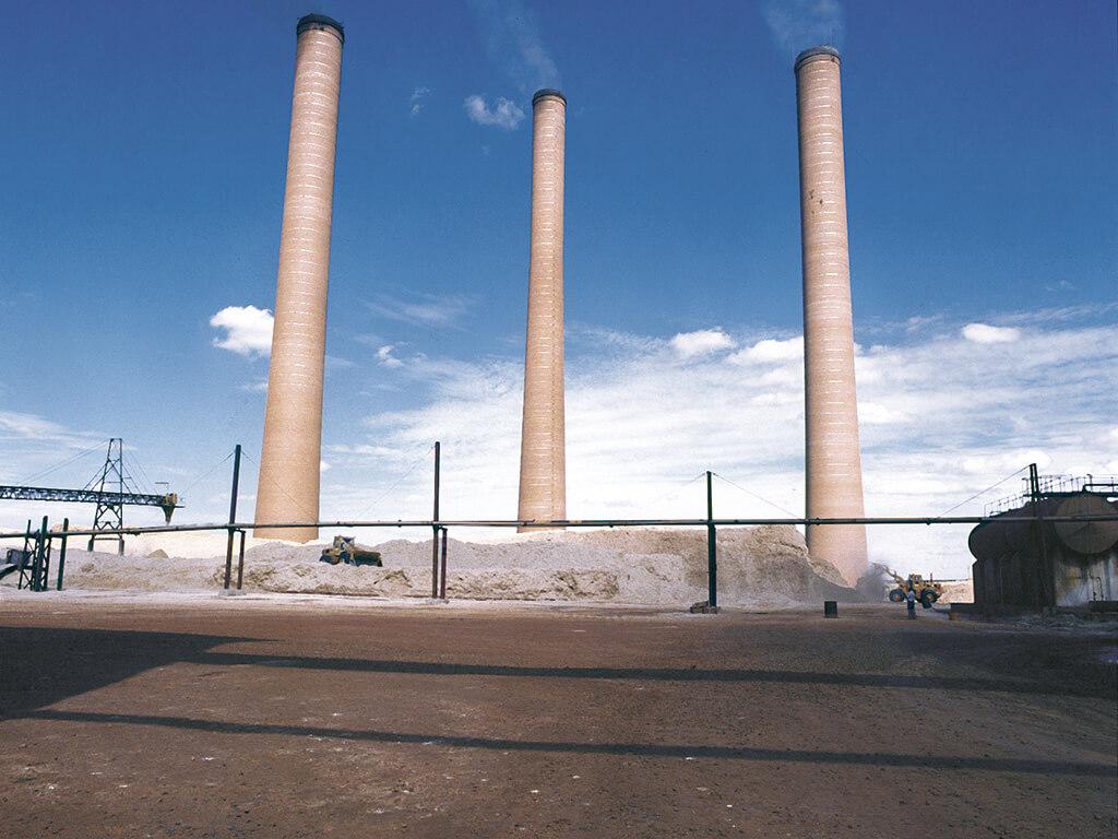 Chaminés em alvenaria. 110m de altura, com 5.000 m³ de concreto ciclópico na base, 1.800.000 tijolos especiais. Execução em prazo de 10 meses.
